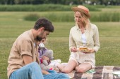 Fotografie happy family with one child eating sandwiches while sitting on plaid at picnic