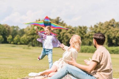 happy family with one child playing with colorful kite in park