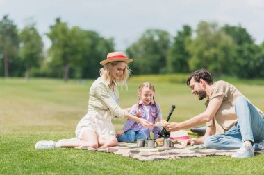 happy family with one child sitting together on plaid at picnic