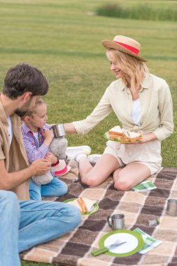 happy family eating sandwiches while sitting on plaid at picnic