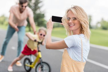 woman holding smartphone and smiling at camera while photographing father teaching daughter riding bicycle