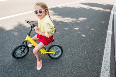 high angle view of cute smiling child in sunglasses riding bicycle