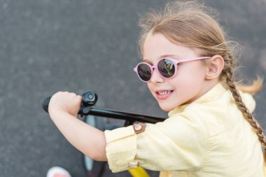 close-up view of cute smiling child in sunglasses riding bicycle