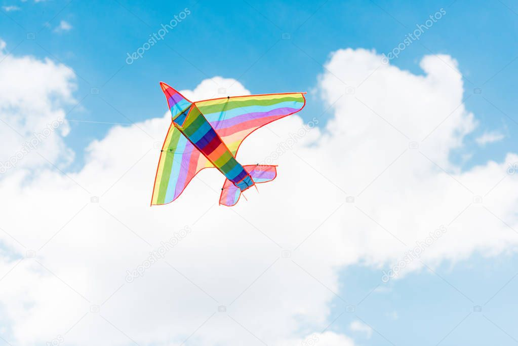 colorful kite flying in blue sky with clouds