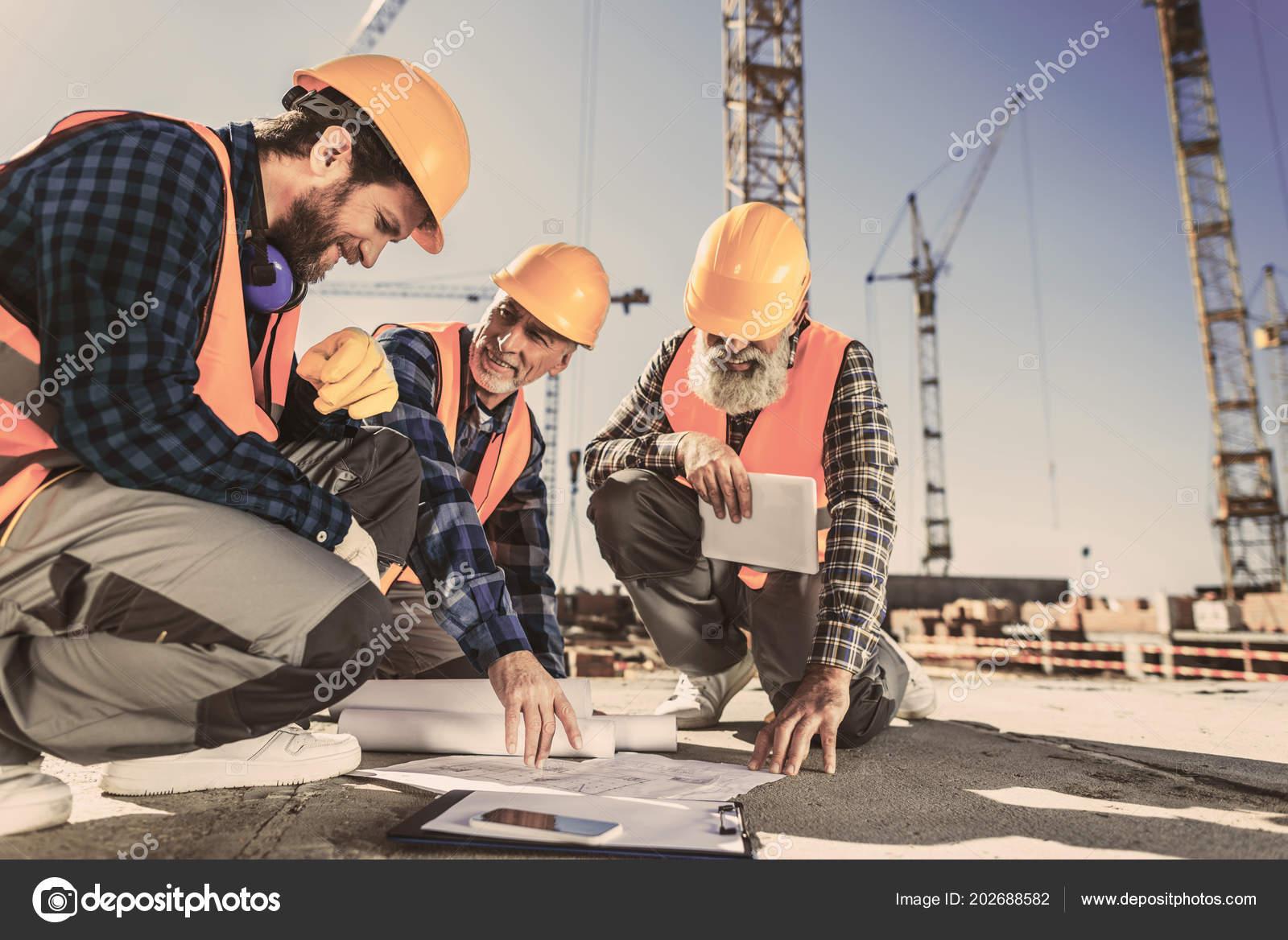 95aa1de3fb606 Construction Workers Sitting Concrete Construction Site Looking Building  Plans– stock image