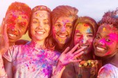 Fotografie happy young multiethnic friends having fun with colorful powder at holi festival and looking at camera