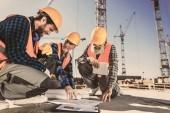 stavební dělníci sedí na betonu na staveništi a při pohledu na stavební plány