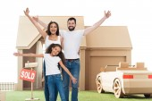Fotografia happy multi ethnic family with raised hands in front of new home