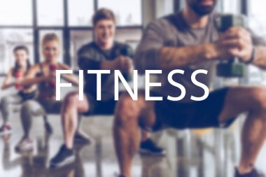 blurred group of athletic young people in sportswear with dumbbells exercising at gym, fitness inscription