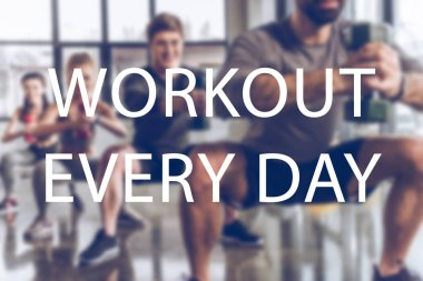 blurred group of athletic young people in sportswear with dumbbells exercising at gym, workout  every day inscription