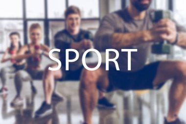 blurred group of athletic young people in sportswear with dumbbells exercising at gym, sport inscription
