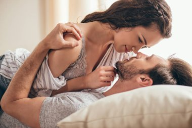 beautiful sensual couple cuddling in bed and looking at each other