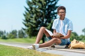 Fotografie smiling african american teenager sitting on skateboard and reading book in park