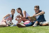 low angle view of smiling teenagers studying with books and digital tablet in park