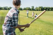 Photo side view of teenage boy holding baseball bat and playing with friends in park