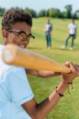 Fotografie selective focus of smiling african american teenager playing baseball with friends in park