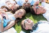 Fotografia vista di alto angolo di felici multietnici amici adolescenti che si trovano insieme sul prato verde