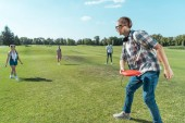 group of happy teenage friends playing with flying disc in park