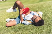 happy african american teenager holding lying disk and lying on grass in park