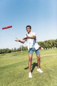 Fotografie full length view of african american teenager with backpack playing with flying disc in park