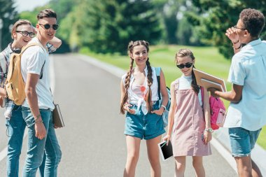 multiethnic group of teenagers with books, backpacks and digital tablet spending time together in park