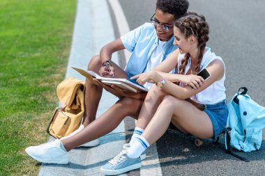 multiethnic teenage boy and girl studying together in park