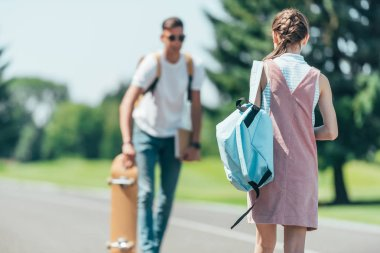 back view of teenage girl with backpack looking at friend with skateboard in park