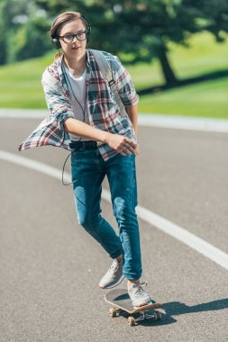 teenage student in headphones riding skateboard and looking away in park