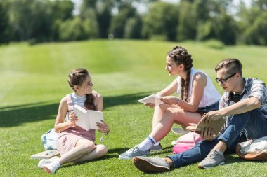 smiling teenage students with books and digital tablet sitting on grass and studying together in park