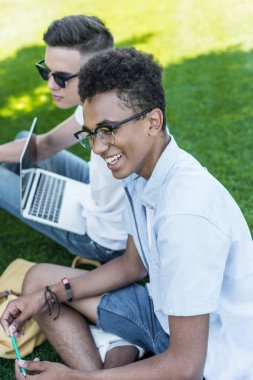 high angle view of multiethnic teenagers smiling and using laptop while studying together on grass