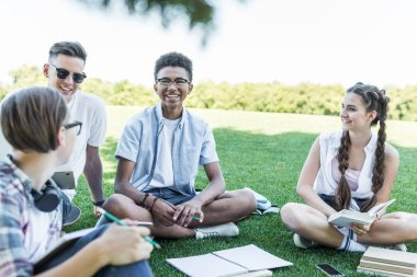 happy multiethnic teenage students sitting on grass and studying together in park