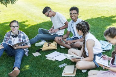 high angle view of smiling multiethnic teenagers sitting on grass and studying in park