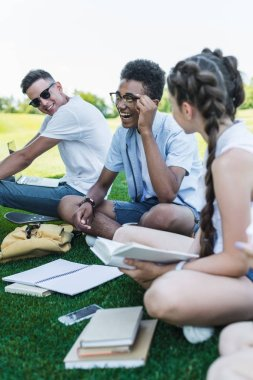 happy multiethnic teenage students smiling while studying together in park