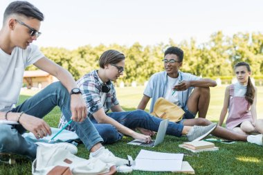 happy multiethnic teenagers sitting and talking while studying together in park