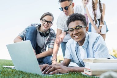 happy multiethnic teenagers using laptop and studying in park