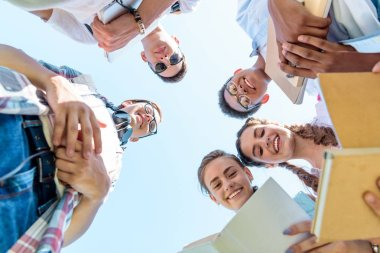 bottom view of happy teenage multiethnic friends holding books and standing together against blue sky