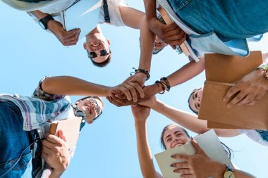 bottom view of smiling multiethnic teenage classmates stacking hands in park