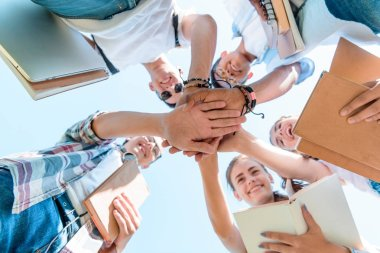 bottom view of happy multiethnic teenage classmates stacking hands in park