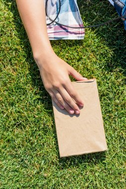 cropped shot of person holding book with blank cover on green grass