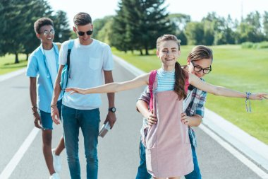 happy multiethnic teenage friends having fun while walking together in park