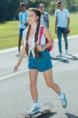 smiling teenage girl with backpack riding skateboard while classmates walking behind in park