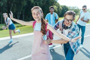 happy multiethnic teenage friends having fun together in park