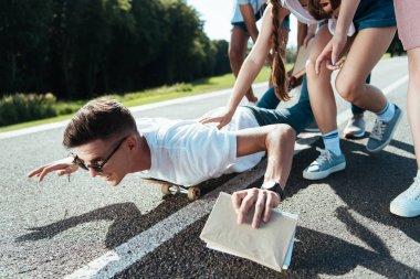 cropped shot of teenagers having fun while friend lying on skateboard