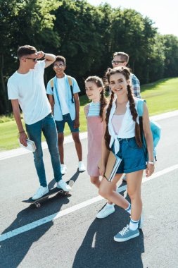 happy multiethnic teenage classmates walking together on park
