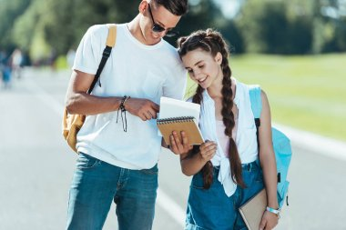 happy teenagers with backpacks holding books while standing and smiling together in park