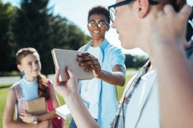 cropped shot of teenager giving book to smiling friend in park