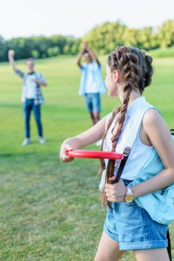 beautiful teenage girl throwing flying disc to friends in park