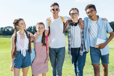 happy multiethnic teenage friends standing together and smiling at camera in park