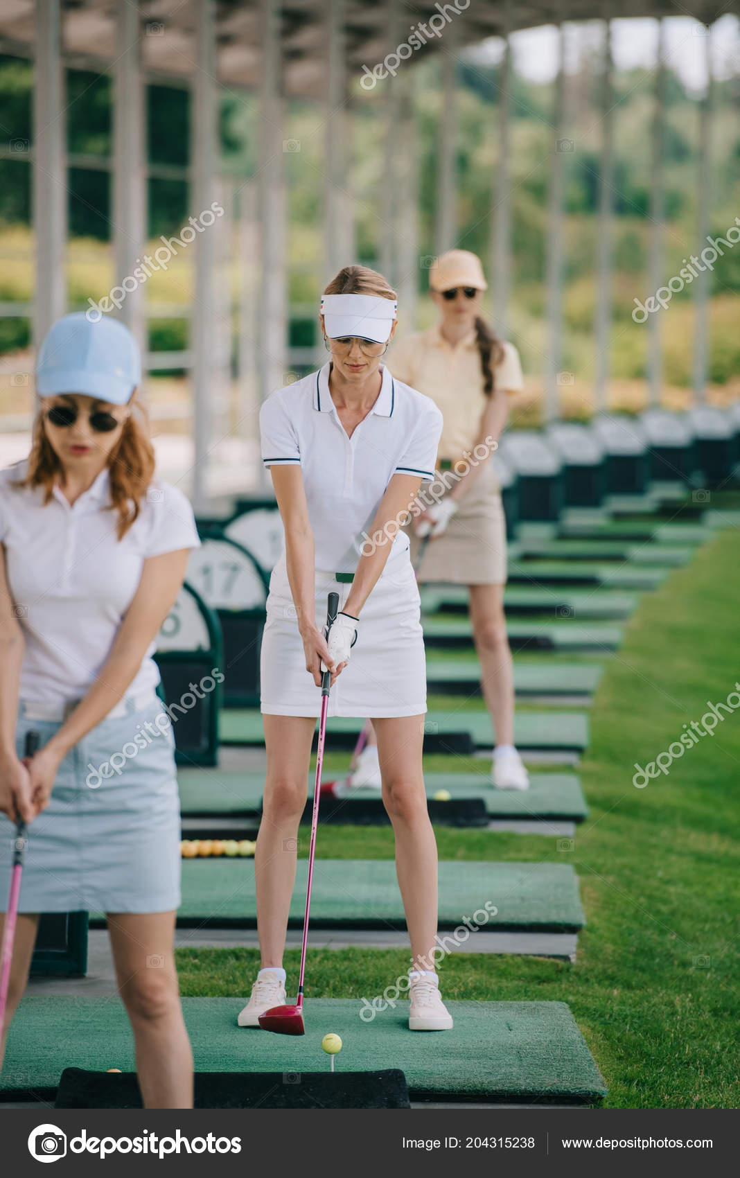 Women playing golf together on course - Stock Image - F007