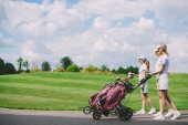 boční pohled na ženské golfisté s golfové vybavení chůzi na golfovém hřišti